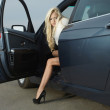 Glamorous blond babe near tuned super car — Stock Photo
