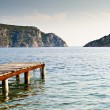 Old pier in rocky bay - Stock Photo