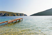 Old pier in rocky bay with awesome transparent water — Stock Photo