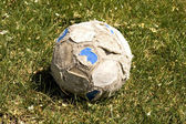 Old soccer ball on the field — Stock Photo