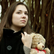 Girl with teddy bear in the park — Stock Photo