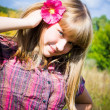 Pretty girl with pink flower in her hair - Stock Photo