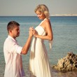 Groom wears ring bride on beach — Stock Photo