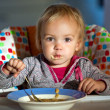 Little girl eats porridge — Stock Photo #7558448