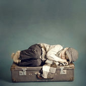 Boy sleeping on a suitcase — Stock Photo