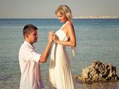 Groom wears ring bride on beach — Stock Photo