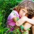 Little girl in the field with flowers — Stock Photo