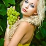 Beautiful blonde girl in green grape — Stock Photo #7562858