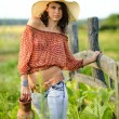 Beautiful girl in a straw hat for a walk in the countryside — Stock Photo