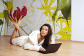 A young woman in a white robe with laptop — Stock Photo