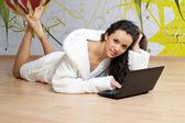Mladá žena v bílém rouchu s notebookem — Stock fotografie