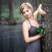 Bella ragazza nel bosco pone con fiori — Foto Stock