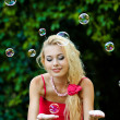 Beautiful blonde girl playing with soap bubbles — Stock Photo #7588921