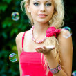 Beautiful blonde girl playing with soap bubbles — Stock Photo