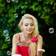 Beautiful blonde girl playing with soap bubbles — Stock Photo #7651173
