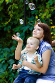 Mom and son playing with soap bubbles — Stok fotoğraf