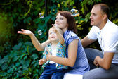 Happy family playing with soap bubbles — Stock Photo