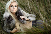 Girl in a fur coat in the autumn background — Stock Photo