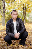 Outdoors portrait of young man in autumn park — Stock Photo