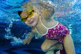 Happy cute girl toddler swimming underwater — Stock Photo