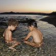 Two little girls playing in water at seaside at dusk — Stock Photo