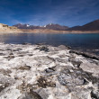 Salty white crust on shore of mountain lake — Stock Photo