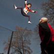 Little girl jumping off roof on trampoline — Stock Photo