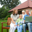 Family watching laptop on the bench in front of the house - Stok fotoğraf
