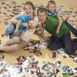 Family having fun on the floor and watching photos - Stockfoto