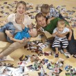 Family having fun on the floor and watching photos — Stock Photo #7709258