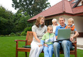Family watching laptop on the bench in front of the house — Stock Photo