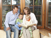 Family reading book — Stock Photo