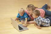 Family watching laptop on the floor — Stock Photo