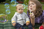 Mother and baby playing bubbles in the garden — Stock Photo