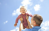 Father tossing baby on sky background — Stock Photo