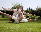 Family playing airplane on grass — Stock Photo
