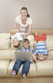 Children and mother on the sofa having fun — Stock Photo