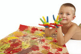 Smiling child with painted hands and art paper — Stock Photo
