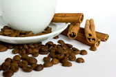 Coffee cup with beans and cinnamon — Stock Photo
