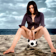 Model on a football at the beach — 图库照片