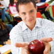 Classroom and teacher with apple — Stock Photo