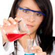 Stock Photo: Female chemist mixing liquids