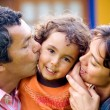 Parents kissing son portrait — Stockfoto
