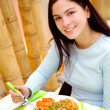 Girl eating in a restaurant — Stock Photo