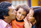 Parents kissing son portrait — Stock Photo