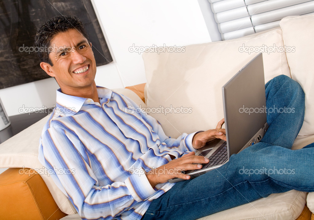Casual entrepreneur working from home looking very relaxed in his sofa browsing the web in his laptop computer — Stock Photo #7568383