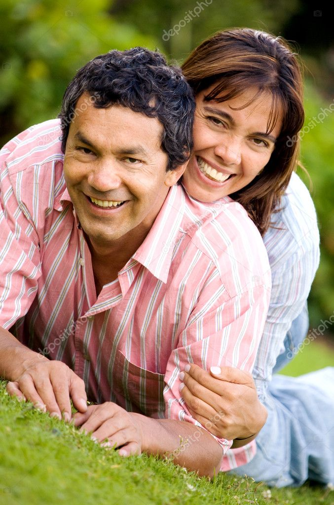 Couple portrait on the floor outdoors where both are smiling and looking happy  Stock Photo #7568418