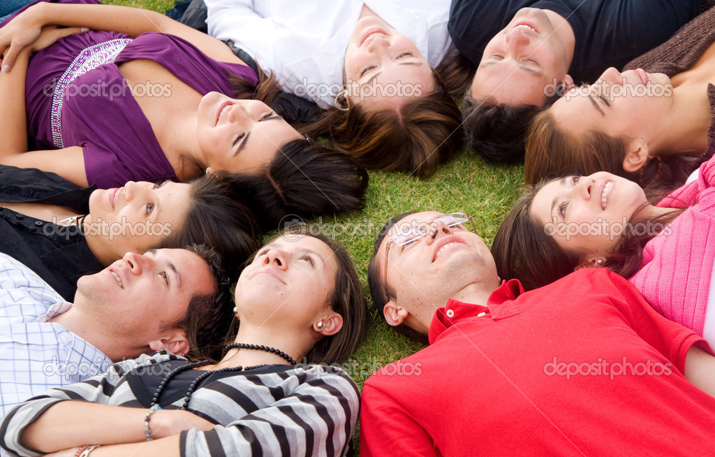 Group of happy friends smiling and relaxing outdoors with heads together on the floor  Stock Photo #7568764