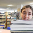 Female student in a library - too much work — Stock Photo