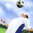 Footballer chesting the ball - Stock Photo